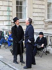 Acteurs en costumes d'époque échangeant une blague tout en attendant les prises de vue filmées.