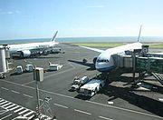 Des avions aux couleurs d'Air France et Air Austral stationnés face à l'aérogare.