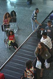 Des passagers fraîchement débarqués d'un vol depuis Paris-Orly attendant leurs bagages sur un carrousel.