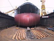 Le gigantisme est illustré en comparant la taille du navire avec celle des ouvriers en contrebas.