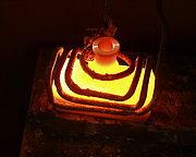 Chauffage par induction d'une bouteille en m�tal�: la variation d'un champ magn�tique induit des courants dans le corps de l'objet, qui �chauffent celui-ci par effet Joule.