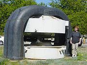 Un électro-aimant de cyclotron au Laurence Hall of Science. Les parties noires sont en acier et se prolongent sous terre. Les bobines de l'aimant sont situées dans les cylindres blancs. La chambre à vide se situerait dans l'espace horizontal entre les pôles de l'aimant.