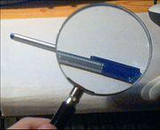 Une loupe, grossissant l'image d'un crayon.
