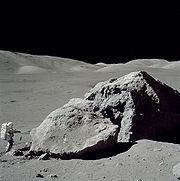 L'astronaute Harrison Schmitt se tenant debout à côté du rocher Taurus-Littrow durant la troisième sortie extra-véhiculaire de la mission Apollo 17.