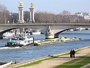 Un pousseur avec 4 barges de sable passe sous un pont de Paris