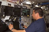 L'astronaute Leroy Chiao utilisant une station de contrôle de Canadarm2 dans le module laboratoire Destiny.