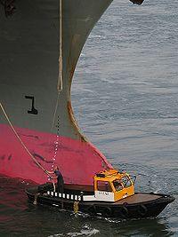 Un bateau de lamanage devant l'étrave d'un porte-conteneurs