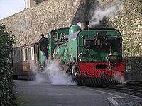 Train tiré par une locomotive à vapeur NGG16s Mileniwm quittant la gare de Caernarfon (Pays de Galles); voie étroite de 2ft.