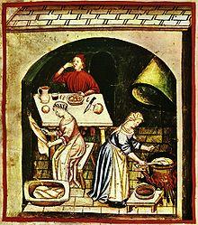 Vignette présentant à l'avant-plan droit une femme debout, touillant dans un chaudron posé dans un cheminée dont on n'aperçoit que la hotte et quelques buches en feu; à gauche, une autre femme, assise, racle au couteau une peau suspendue devant elle; au fond et au centre, un homme, attablé devant un plat, un pichet, un verre, un couteau et deux miches rondes, porte de la nourriture à sa bouche. Les femmes sont habillées de couleurs pastel, bleu et rose, et toutes deux portent une coiffe; l'homme est habillé et coiffé de rouge. La hotte de la cheminée d'un jaune-vert laisse penser qu'elle est en laiton.