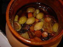 Dans un plat en terre cuite vernissée, les morceaux de viande et légumes carottes, pomme de terre) ont mijoté dans le vin rouge.