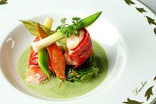 Au centre d'une assiette blanche, décorée de feuillages et marquée du nom Lameloise sur le bord, des morceaux de homard, surmontés de fragments de petits poireaux et de persil plat, trônent dans une sauce mousseuse verte.