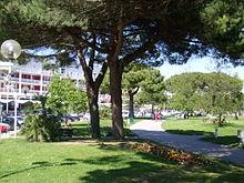 Photographie montrant des allées sablées bordées de pelouse, des massifs fleuris qui serpentent entre les pins parasols et des arbres exotiques. Au fond, les immeubles blancs et rouges du front de mer