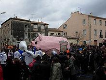 Une foule promenant un gros cochon rose en carton pâte