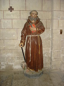 Statue polychrome représentant un moine en robe de bure avec un cochon à ses pieds
