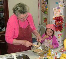 Une grand-mère portant un tablier bordeaux sur une blouse rose, racle au-dessus du plat en inox de pâte qu'elle vient de confectionner l'un des fouets de son mieur-batteur tandis qu'à côté d'elle sa petite-filles habillée de rose fuchsia et portant un tablier identique mais rose pâle, se lèche le doigt utilisé pour gouter la pâte prélevée sur le second fouet.