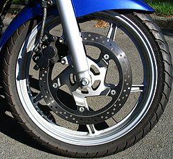 Un frein à disque de moto. Ce disque est perforé, l'étrier est à double piston. Sa commande est hydraulique.