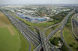 Le réseau autoroutier favorise la création de zones d'activité au détriment des zones distantes, victimes d'un exode des travailleurs et des activités, exacerbant le besoin de transport (A1-A104 /Paris-Nord II, en 2006)
