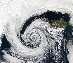 Le sens de rotation de cette basse pression tournant au large de l'Islande dans le sens contraire des aiguilles d'une montre est dû aux effets combinés de la force de Coriolis et du gradient de pression.