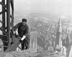 Un skyboy, ouvrier travaillant sur le chantier de l'Empire State Building, sans protection au dessus du vide. Au second plan, le Chrysler Building.