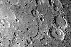 Discovery Scarp (au centre), l'un des plus importants escarpements photographiés par Mariner 10. Il mesure 350km de long et coupe deux cratères de 35 et 55km de diamètre.