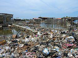 Des banlieues, des bidonvilles ou des routes (ici à Haïti) ont souvent été construits sur des zones humides comblées avec des déchets pour partie fermentescible, avec risques sanitaires, d'effondrement et d'explosion de poches de méthane.