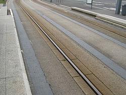 Tramway sur pneus: rail de guidage et voie. Noter les ornières rechappées (Caen).