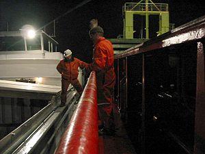 Un docker (le signaleur) se tient sur l'hiloire pendant le chargement, pour guider le grutier.
