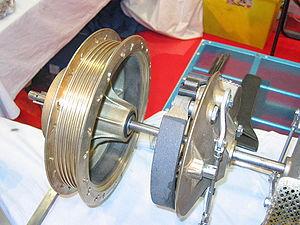 Le frein à tambour d'une moto: à gauche, le tambour, à droite les garnitures. On distingue la came en haut.