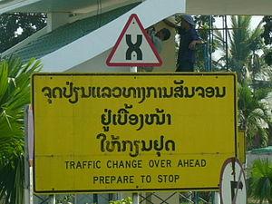 Panneau indiquant un changement de sens de circulation à la frontière entre le Laos (conduite à droite) et la Thaïlande (conduite à gauche)