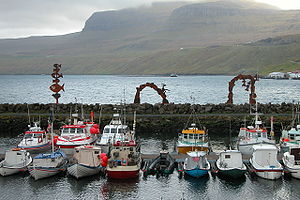 Flottille de pêche aux îles Féroé, mêlant chalutiers modernes à l'arrière-plan et embarcations traditionnelles à l'avant-plan.