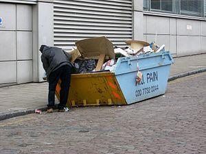 Benne à ordures à Londres, fouillée par une personne pauvre y récupérant des déchets réutilisables.