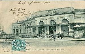 La gare de la Place Denfert-Rochereau, à l'époque où elle était le terminus de la ligneConçue du temps de la voie large du système Arnoux, la forme courbe des bâtiments permettait aux trains de desservir le terminus en tournant le long de la façade intérieure.