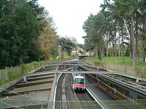 Une rame entre en station à Cité Universitaire dans le Parc Montsouris à Paris.