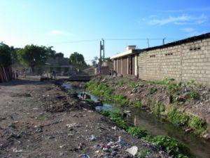Absence d'assainissement à Cap-Haïtien, Haïti: les déchets à même le sol (incluant des sacs plastiques remplis d'excréments) bloquent les canaux de drainage qui débordent à la moindre pluie, et endommagent les infrastructures à côté (routes, bâtiments…).