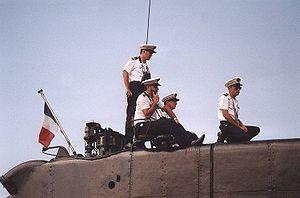 Noter sur cette photographie du massif du sous-marin français Doris, le tube d'échappement à l'arrière et la tête du tube d'air juste devant le pavillon