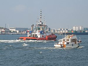 Un petit bateau de plaisance et un remorqueur à Rotterdam.