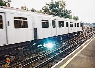 Système à quatre rails du métro de Londres avec deux rails électriques, le rail positif ayant une tension double de celle du rail négatif. Des arcs électriques se produisent couramment à la fin des sections de rail.