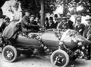 Camille Jenatzy auf der Siegesparade am 1. Mai 1899 in Achères nach der 100 km/h Rekordfahrt am 29. April 1899