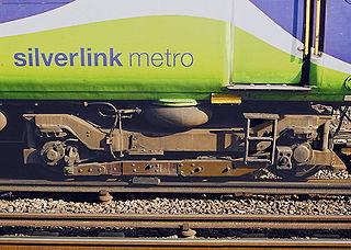 Frotteur fixé au bogie par l'intermédiaire d'une poutre en bois, sur une rame Classe 313 du réseau Silverlink (nord-ouest de Londres).