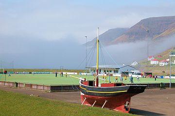 Fodboldbane i Sørvágur, Færøerne, un sloop au premier plan.