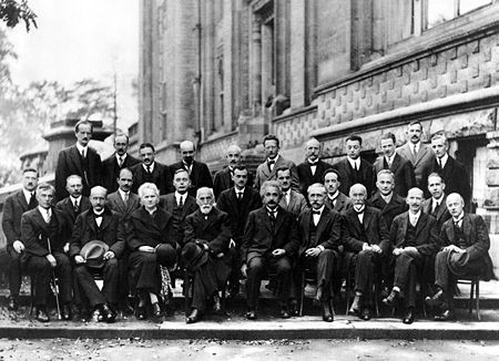 A. Piccard, E. Henriot, P. Ehrenfest, Ed. Herzen, Th. De Donder, E. Schrödinger, E. Verschaffelt, W. Pauli, W. Heisenberg, R.H. Fowler, L. Brillouin, P. Debye, M. Knudsen, W.L. Bragg, H.A. Kramers, P.A.M. Dirac, A.H. Compton, L. de Broglie, M. Born, N. Bohr, I. Langmuir, M. Planck, Mme. Curie, H.A. Lorentz, A. Einstein, P. Langevin, Ch. E. Guye, C.T.R. Wilson, O.W. Richardson Les participants au cinquième Conseil, 1927. Institut International de Physique Solvay (Parc Léopold de Bruxelles).