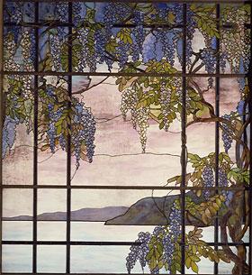 Vitrail de Tiffany avec son verre opalescent caractéristique. Le dessin asymétrique est réalisé par la combinaison de verres colorés et d'un décor peint qui joue avec la trame régulière des cadres.
